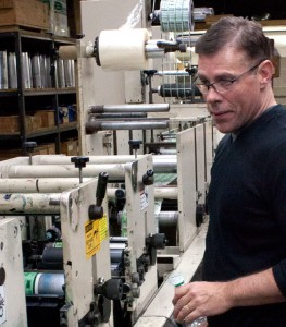 John O'Connor, sole owner of United Label Corporation, manufacturer of custom pressure sensitive labels, checking out one of his machines